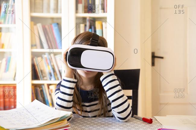 Girl sitting at table at home using virtual reality glasses