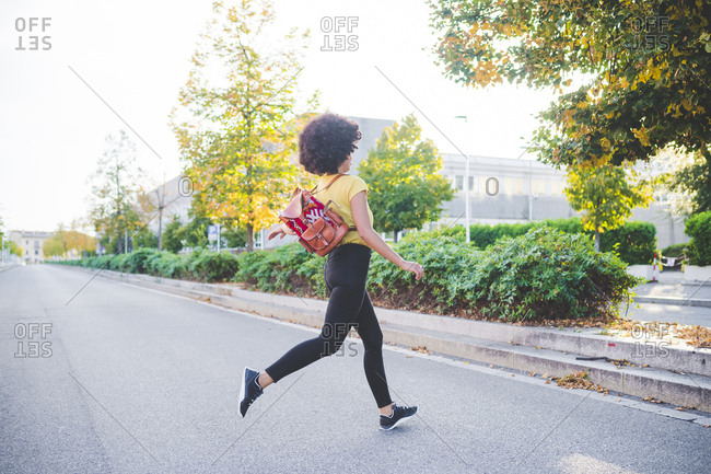 Young woman with afro hairdo running on a street in the city