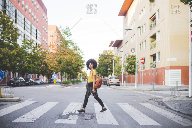 Young woman with afro hairdo walking in the city