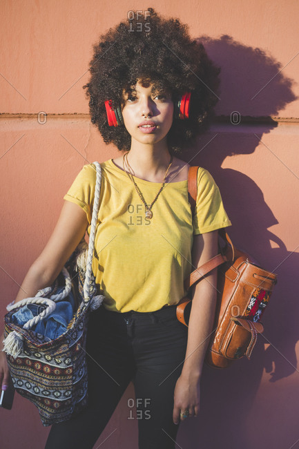 Portrait of young woman with afro hairdo listening to music with headphones