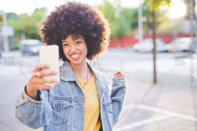 Happy young woman with afro hairdo taking a selfie in the city