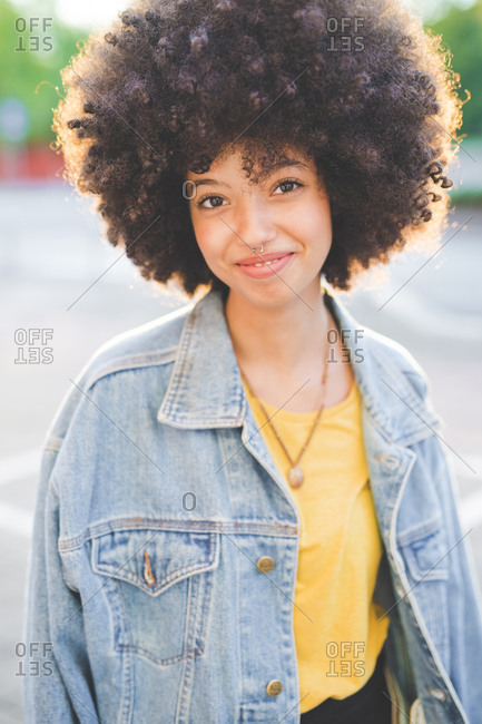 Portrait of young woman with afro hairdo in the city