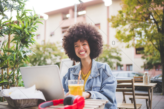 Happy young woman with afro hairdo using laptop at an outdoor cafe in the city