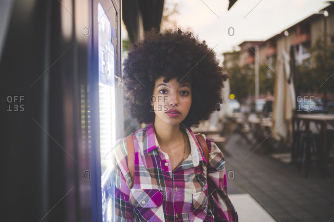 Portrait of young woman with afro hairdo in the city at dusk