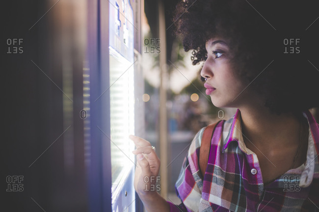 Young woman with afro hairdo using touchscreen vending machine in the city