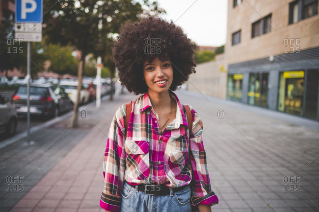 Portrait of smiling young woman with afro hairdo in the city