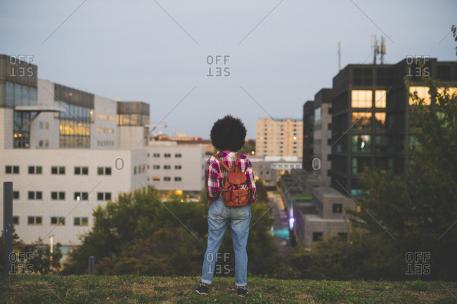Rear view of young woman with afro hairdo looking at cityscape- Milan- Italy