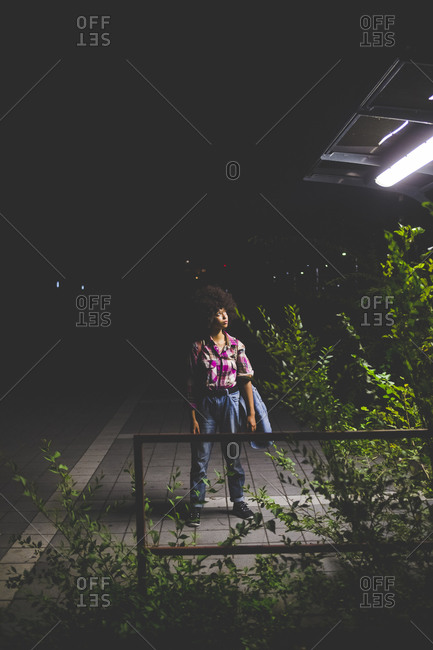 Young woman with afro hairdo standing on platform at night