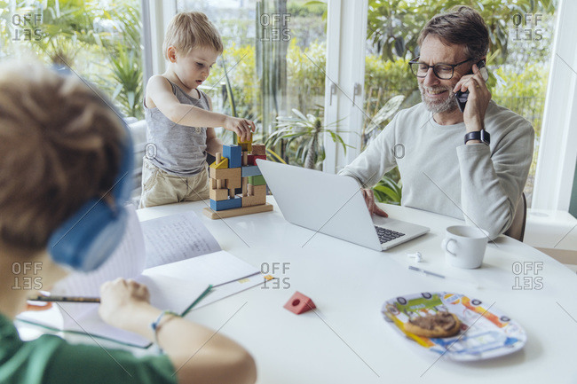 Father talking on the phone while sons are playing on the table