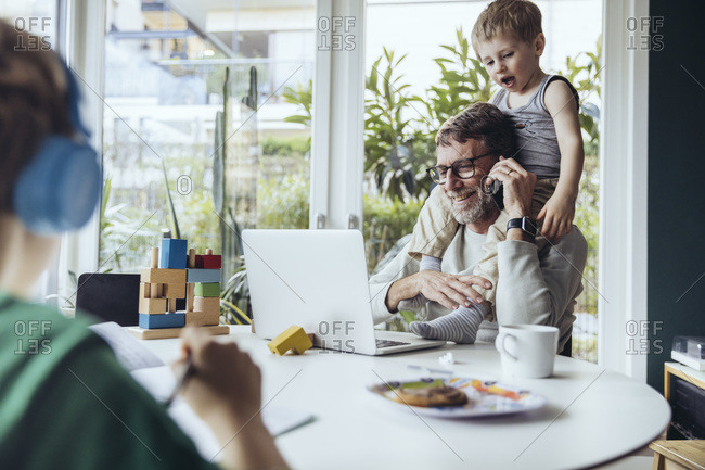 Father working from home- talking on the phone- while children are playing