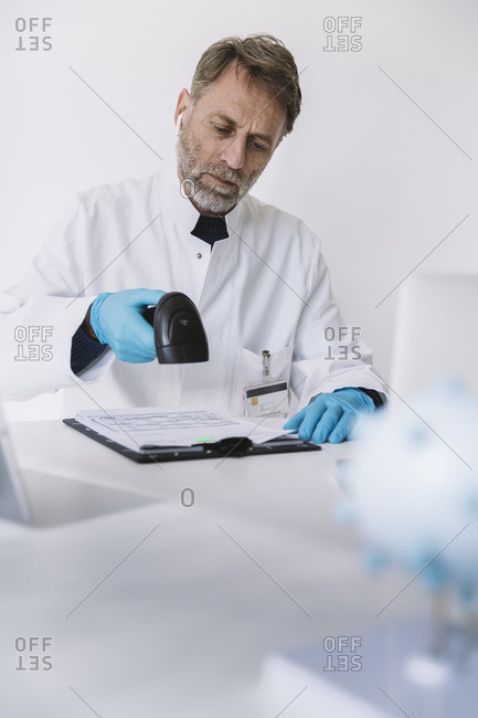 Scientist scanning forms at desk