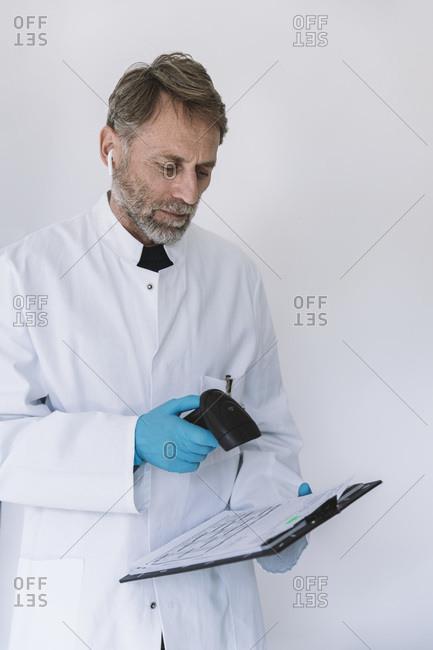 Scientist scanning forms in lab