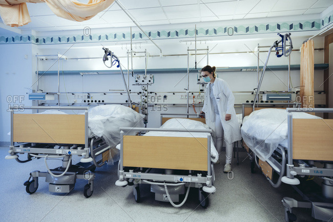 Doctor in hospital room with empty beds