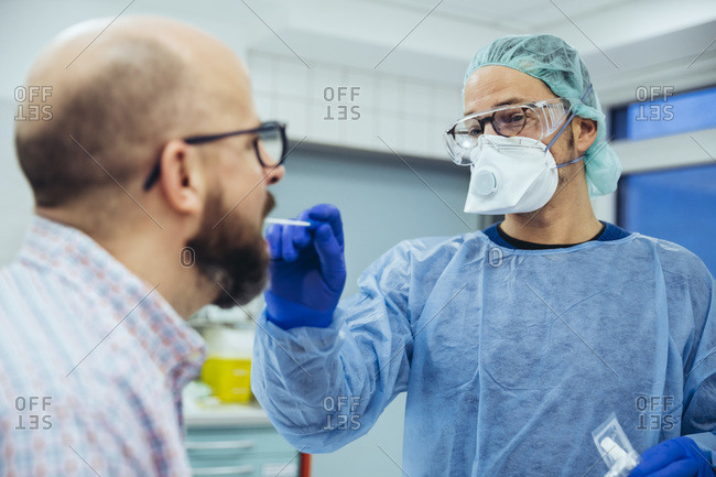 Doctor in hospital taking a swab from patient's mouth