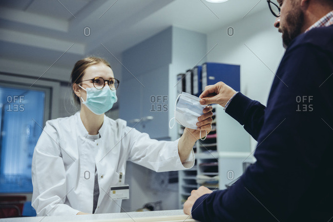Employee at reception desk of hospital ward handing over mask to visitor