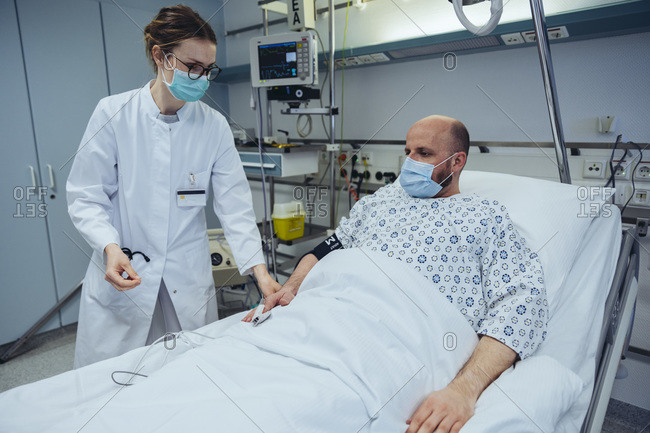 Doctor connecting patient to pulse tracer in hospital room