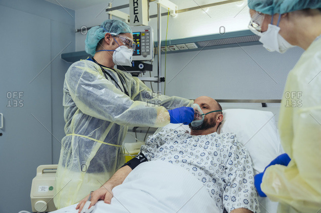 Doctors caring for patient in emergency care unit of a hospital with respiratory equipment