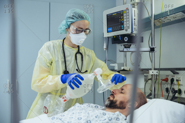 Doctor with bag valve mask caring for patient in emergency care unit of a hospital