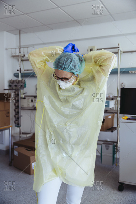 Doctor taking off personal protective equipment in hospital