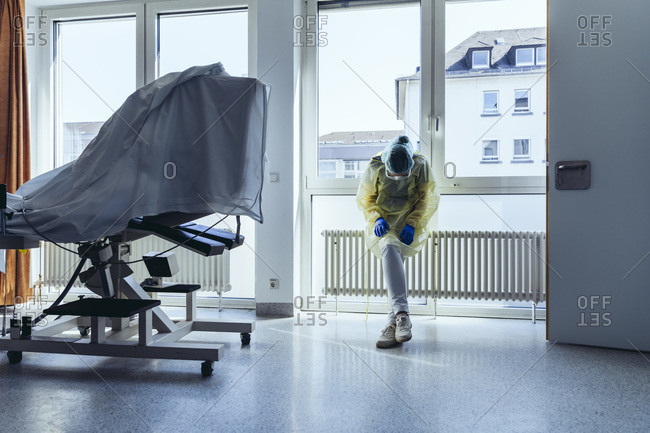 Exhausted doctor wearing personal protective equipment in hospital