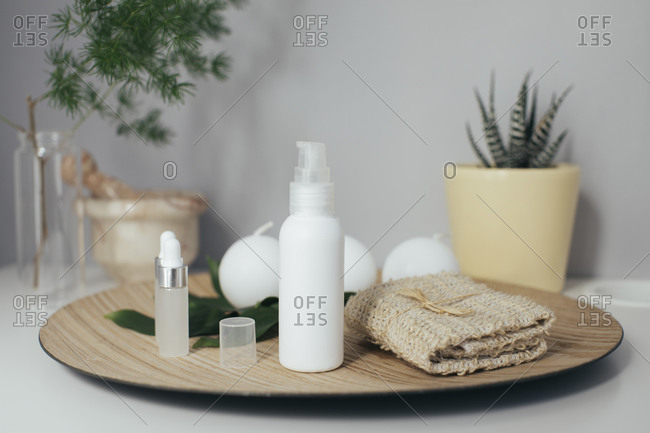 Beauty products on wooden plate