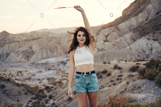Portrait of happy young woman with sparkler at sunset- Almeria- Spain