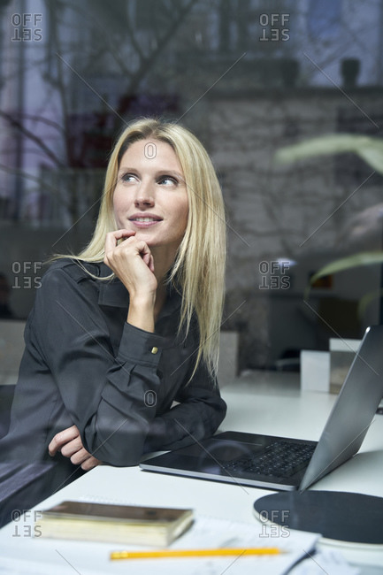 Portrait of smiling blond woman with laptop behind windowpane in office