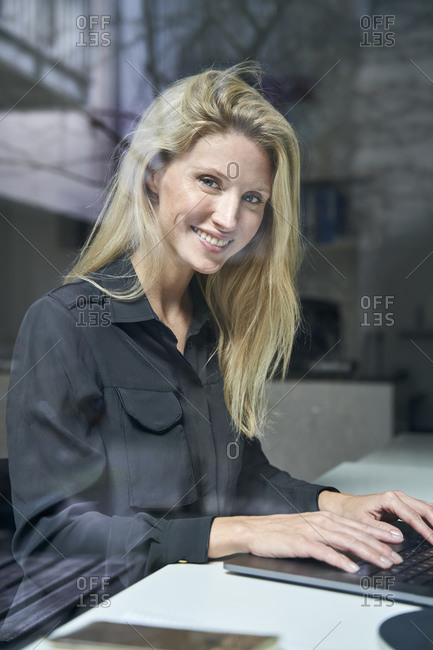 Portrait of smiling blond woman using laptop behind windowpane in office
