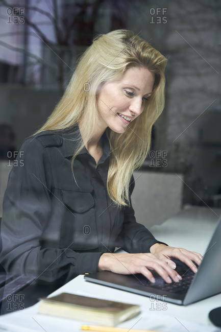 Smiling blond woman using laptop behind windowpane in office