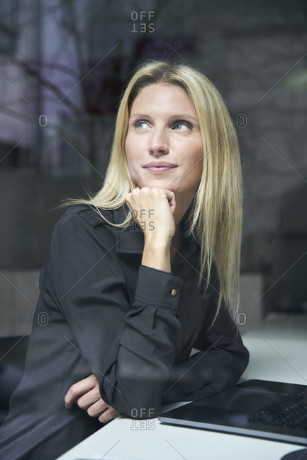 Portrait of blond woman with laptop behind windowpane in office