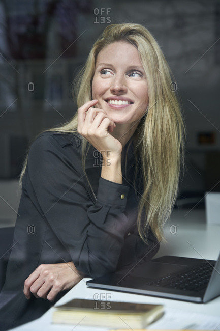 Portrait of happy blond woman with laptop behind windowpane in office