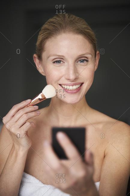 Portrait of beautiful woman applying make up