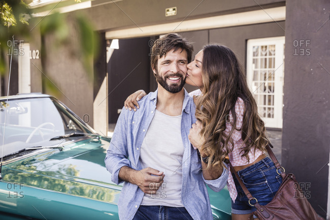 Happy couple at a convertible car outside house