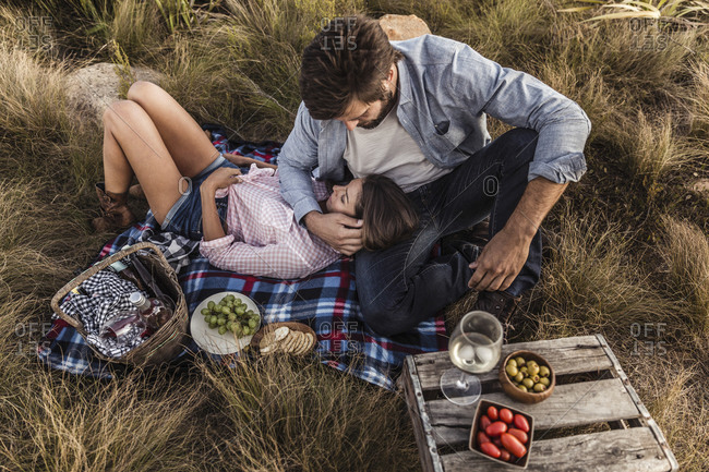 Affectionate couple having a picnic in the countryside