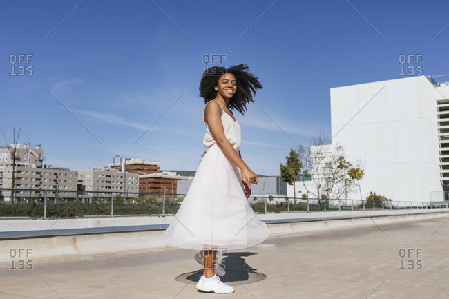 Happy young woman dancing on a sunny day
