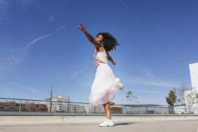 Happy young woman dancing in a summer dress