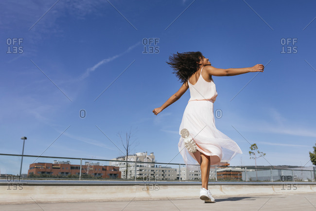 Happy young woman dancing in sneakers