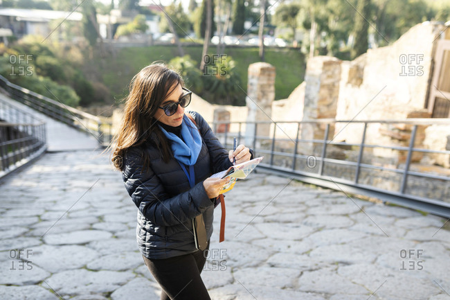 Female tourist using map on a city break in Naples- Italy