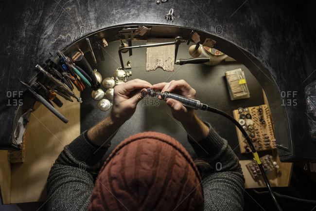 Goldsmith working on ring in his workshop- from above