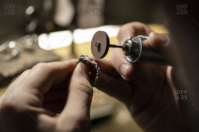 Close-up of a goldsmith hand's grinding a silver ring
