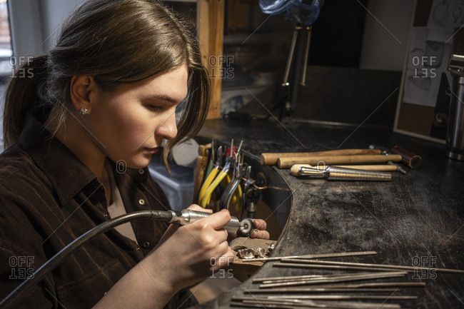 Female goldsmith working with grinder on silver ring