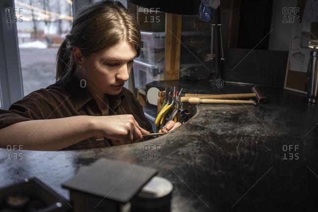 Female goldsmith working on her workbench in the workshop