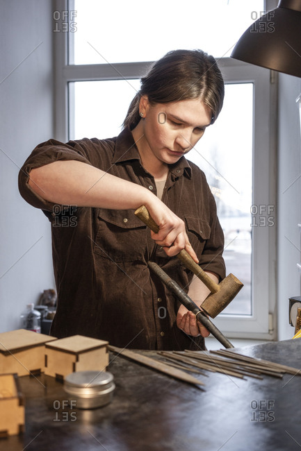 Female goldsmith working on ring in her workshop