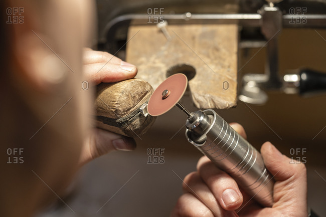 Hand of female goldsmith working with grinder on silver ring