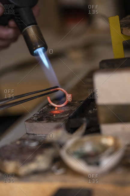 Goldsmith working with bunsen burner on ring