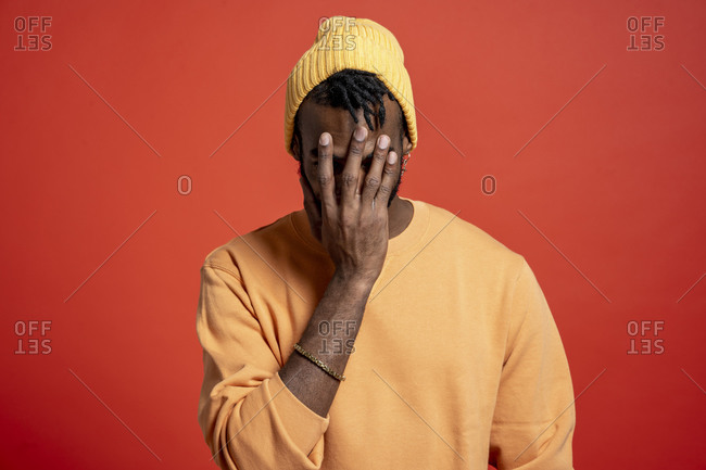 Young man covering his face in front of orange wall