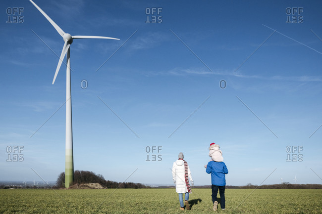 Back view of parents with little daughter walking on a field with wind wheel in the background