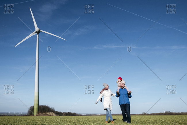 Happy parents with little daughter walking on a field with wind wheel in the background