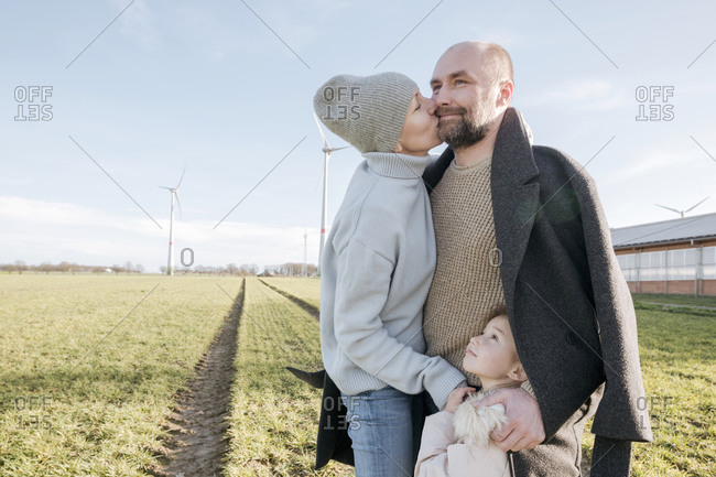 Happy parents with little daughter standing on a field in winter