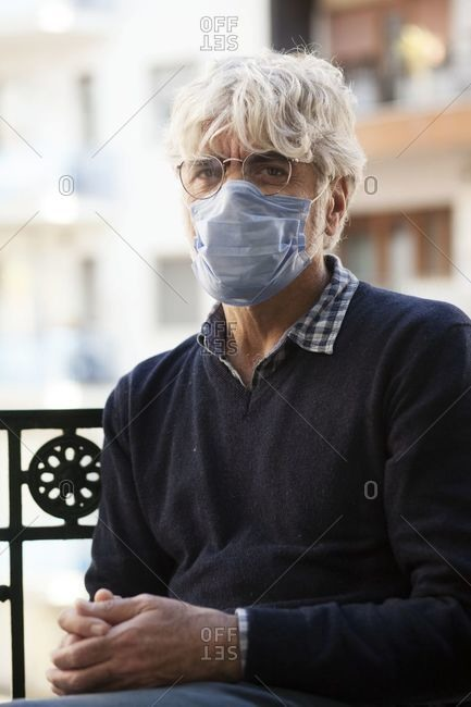 Naples, Italy - April 4, 2020: Man sitting outside while wearing personal protective equipment